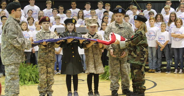 Picture of students folding flag at the ceremony.