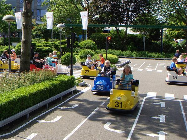students driving toy cars